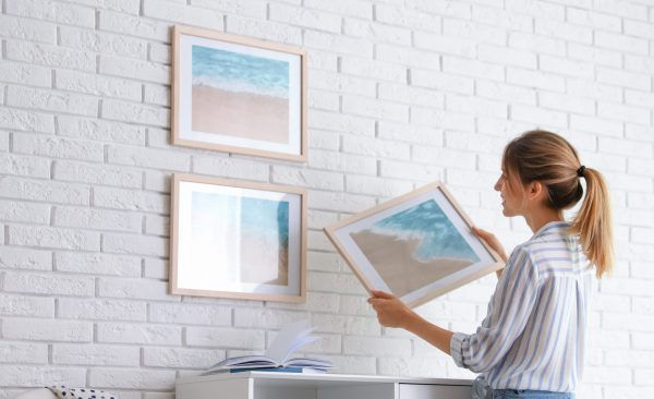 woman hanging artwork on the wall